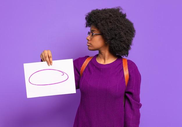 Молодая афро-женщина-студентка в профиле, желающая скопировать пространство впереди, думать, воображать или мечтать