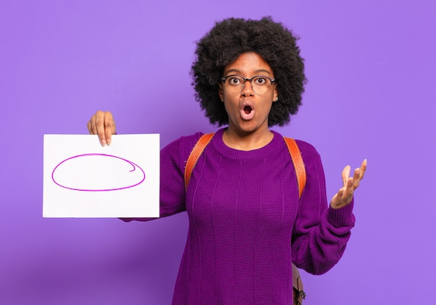 Young student afro woman open-mouthed and amazed, shocked and astonished with an unbelievable surprise