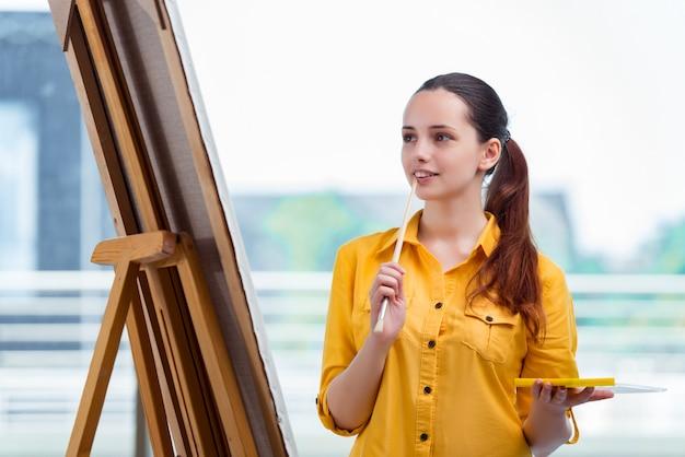 若い学生アーティストのスタジオで絵を描く