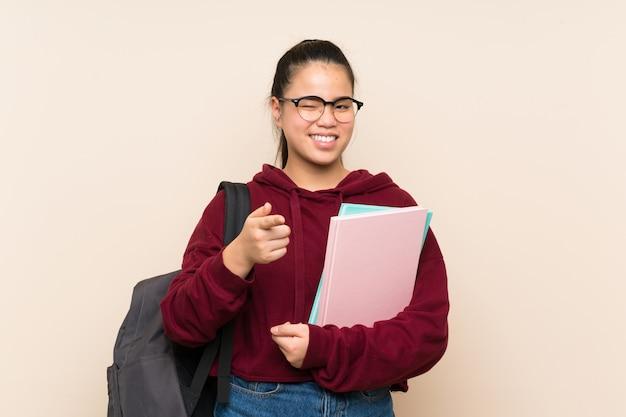 孤立した壁の上の若い学生アジアの女の子の女性があなたに指を指す