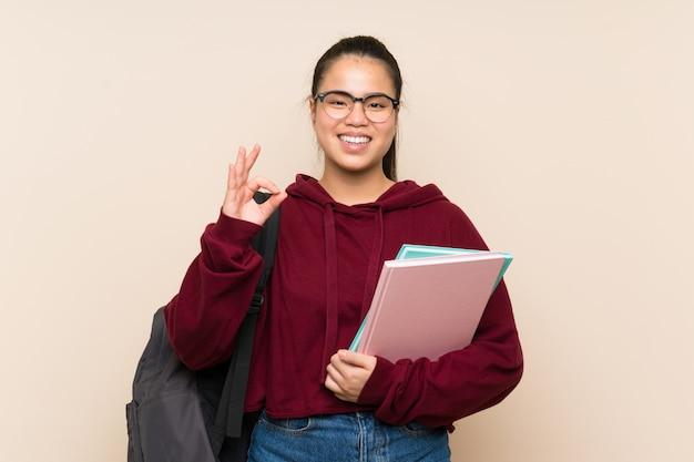 指でokサインを示す孤立した壁の上の若い学生アジアの女の子女性