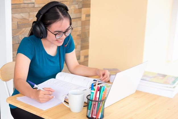 헤드폰과 안경을 쓴 아시아 10대 소녀가 학교에서 온라인 학습을 하는 랩톱 컴퓨터를 보며 행복하게 웃고 있습니다. 집에서 대학 화상 통화 원격 교육 수업