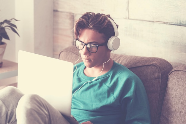 インターネット接続で勉強する現代のラップトップ コンピューターとヘッドフォンを自宅にいる若い学生