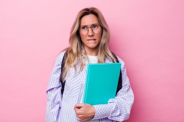 분홍색 배경에 고립 된 젊은 학생 호주 여자는 혼란 스 러 워, 의심스럽고 확신을 느낍니다.