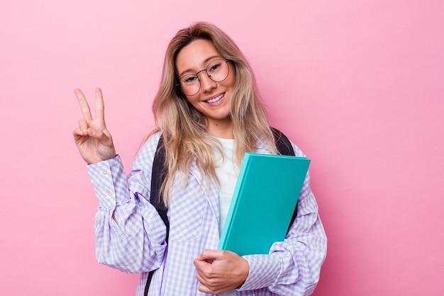 ピンクの背景に隔離された若い学生オーストラリア人女性は、指で平和のシンボルを示して楽しくてのんき。
