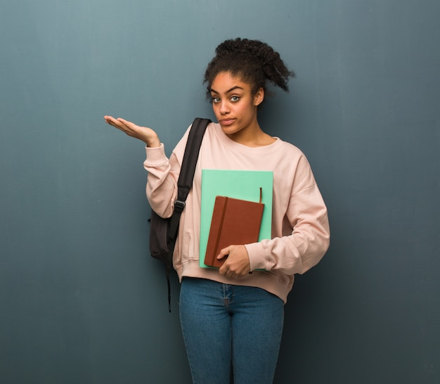 Young student black woman confused and doubtful. she is holding books.