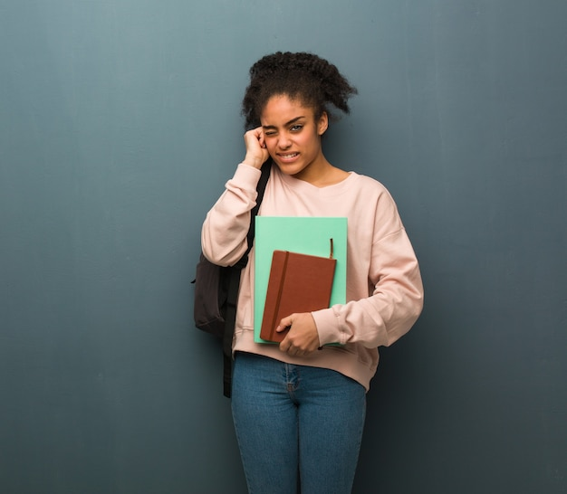 Young student black woman covering ears with hands. she is holding books.