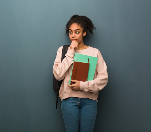 Young student black woman doubting and confused. she is holding books.