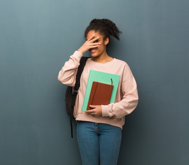 Young student black woman embarrassed and laughing at the same time. she is holding books.