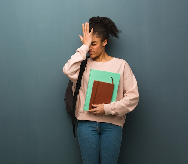 Young student black woman forgetful, realize something. she is holding books.