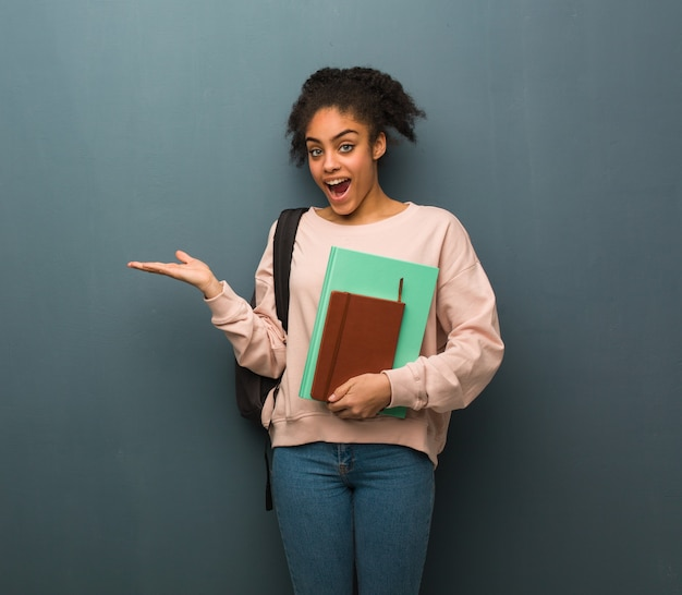 Young student black woman holding something with hand. she is holding books.