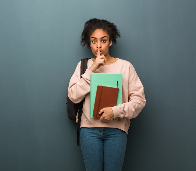 Young student black woman keeping a secret or asking for silence. she is holding books.