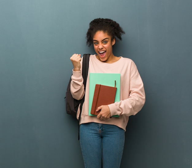 Young student black woman surprised and shocked. she is holding books.