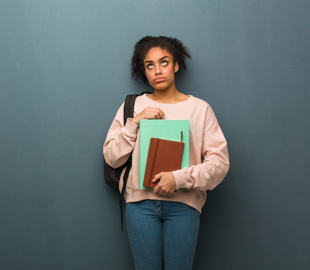 若い学生の黒人女性は疲れて退屈しています。彼女は本を持っています。