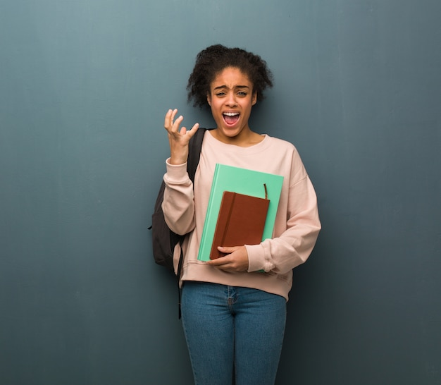 Young student black woman very scared and afraid. she is holding books.