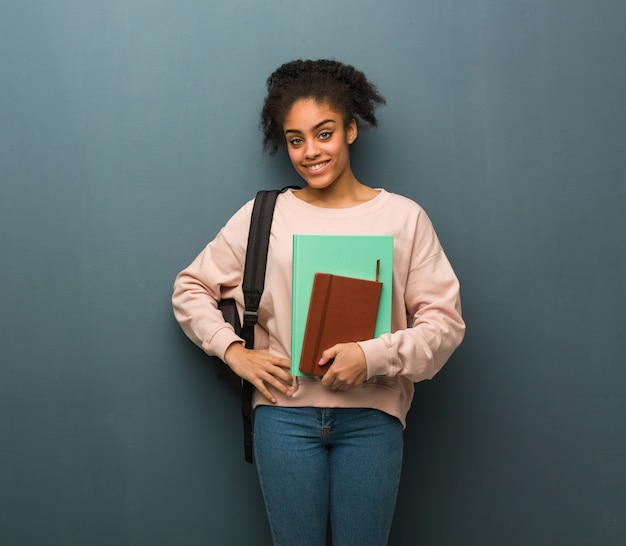 Young student black woman with hands on hips. she is holding books.
