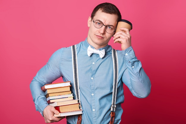 Young student in blue shirt in one tone, looks sleepy and exuasted, holds coffee near head and huge stack of books