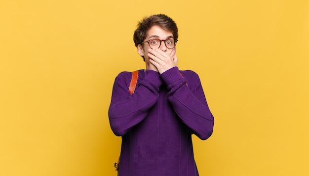Молодой студент мальчик закрывает рот руками с шокированным, удивленным выражением лица, хранит секрет или говорит: ой