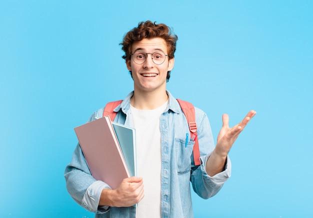 Молодой студент мальчик чувствует себя счастливым, удивленным и веселым, улыбается с позитивным настроем, реализует решение или идею