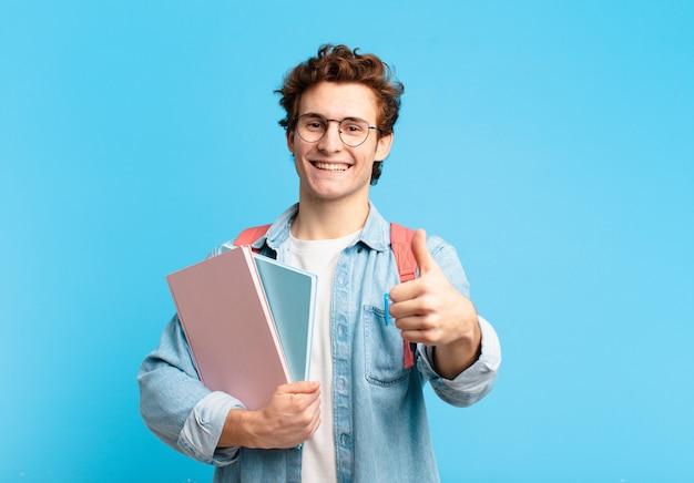 자랑스럽고, 평온하고, 자신감 있고, 행복하고, 엄지 손가락으로 긍정적으로 웃고있는 젊은 학생 소년