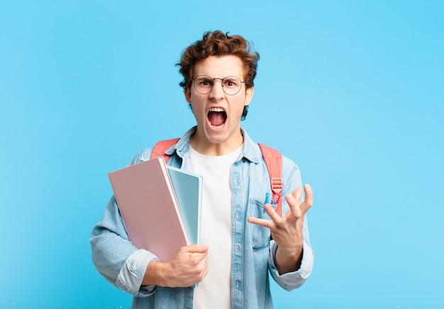 Молодой студент мальчик выглядит сердитым, раздраженным и расстроенным, кричит, черт возьми, или что с тобой не так