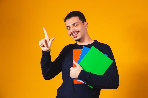 Молодой студент мальчик на желтом фоне. счастливый студент мальчик держит ноутбук