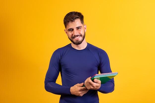Молодой студент мальчик на желтом фоне. счастливый студент мальчик