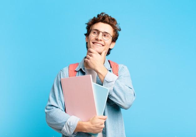 幸せに笑って、空想にふけったり、疑ったり、横を向いている若い学生の男の子