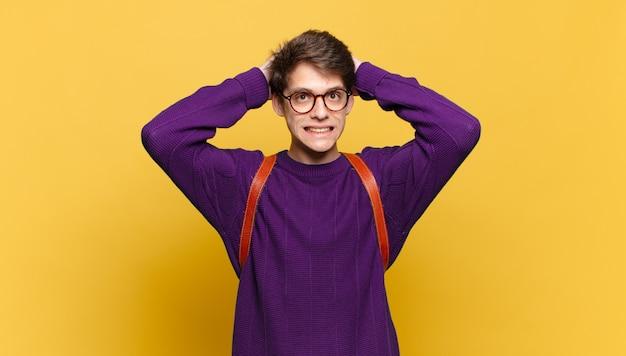 주황색 벽에 학교 가방을 든 어린 학생 소년