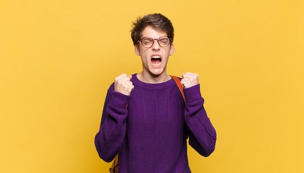 Молодой студент мальчик со школьной сумкой у оранжевой стены