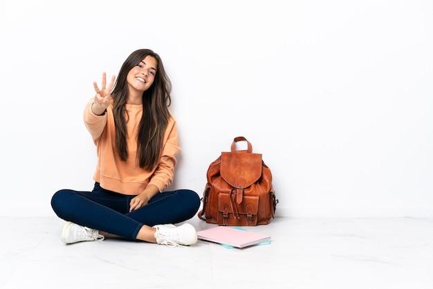 Молодая студентка из бразилии счастлива сидит на полу и считает три пальцами