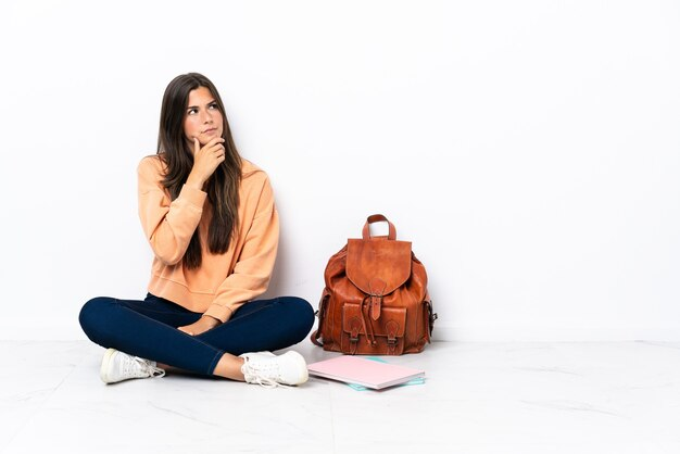 의심을 가지고 혼란스러운 얼굴 표정으로 바닥에 앉아 젊은 학생 브라질 여자
