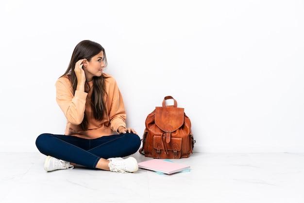 귀에 손을 넣어 뭔가를 듣고 바닥에 앉아 젊은 학생 브라질 여자
