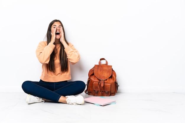 Молодая бразильская студентка сидит на полу, кричит и что-то объявляет