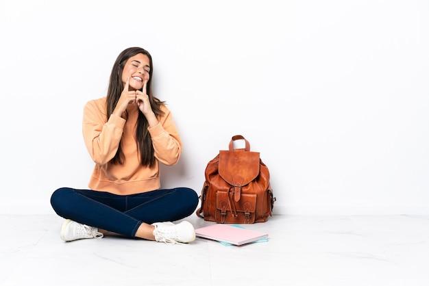 幸せで楽しい表情で笑って床に座っている若い学生ブラジル人女性
