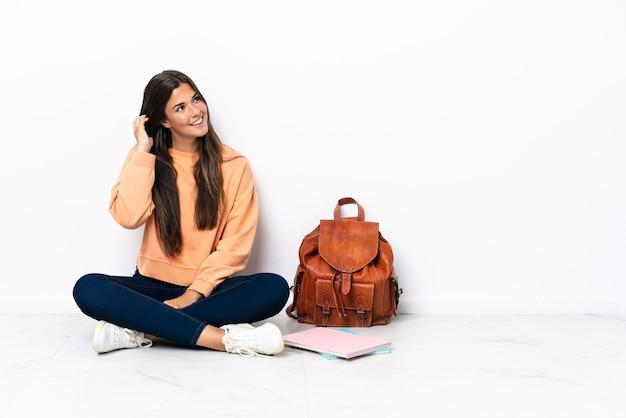 아이디어를 생각하는 바닥에 앉아 젊은 학생 브라질 여자