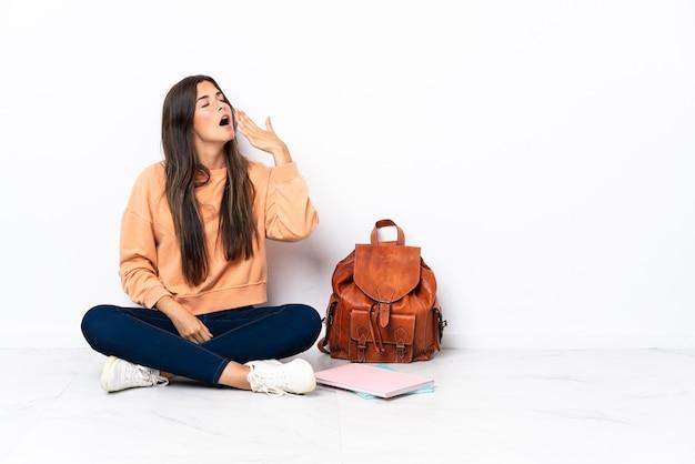 Молодая бразильская студентка сидит на полу, зевая и прикрывая широко открытый рот рукой