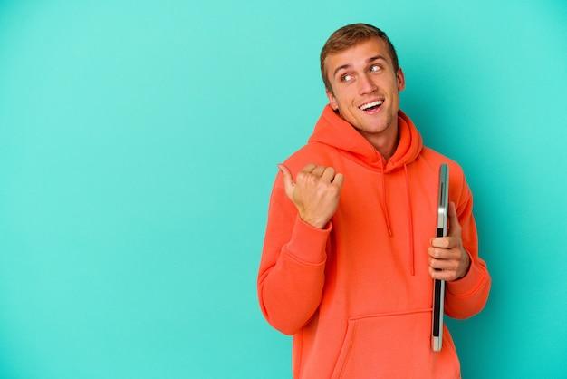 青の背景に分離されたラップトップを保持している若い学生の白人男性が、親指を離して、笑い、屈託のないポイントをポイントします。