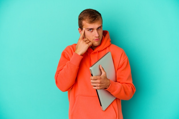 젊은 학생 백인 남자 손가락으로 사원을 가리키는 파란색 벽에 고립 된 노트북을 들고 생각, 작업에 초점을 맞춘.
