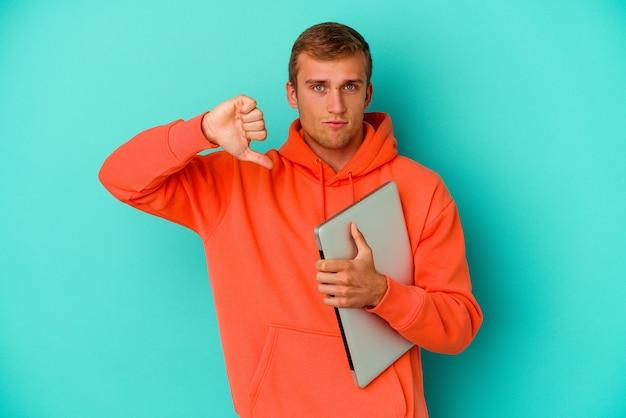 嫌いなジェスチャーを示す青い壁に分離されたラップトップを持っている若い学生の白人男性は、親指を下に向けます。不一致の概念。