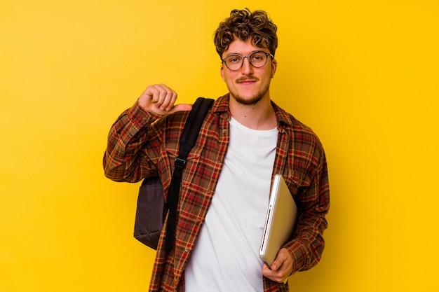 黄色の背景で隔離されたラップトップを持っている若い学生の白人男性は、誇りと自信を持って感じています。 Premium写真