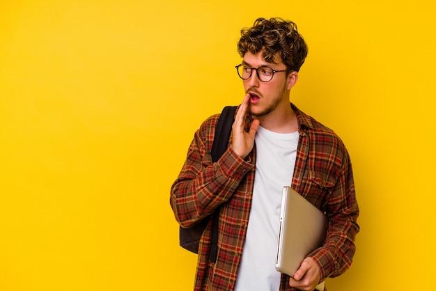 노란색 배경에 고립 된 노트북을 들고 젊은 학생 백인 남자는 비밀 뜨거운 제동 뉴스를 말하고 옆으로 찾고