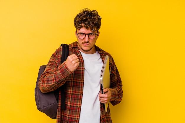 カメラに拳、攻撃的な表情を示す黄色の背景で隔離のラップトップを保持している若い学生白人男性。