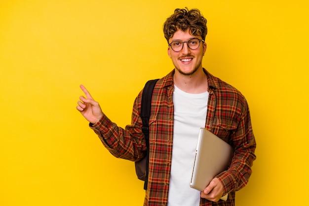 黄色の背景に分離されたラップトップを持っている若い学生の白人男性は、笑顔で脇を指して、空白のスペースで何かを示しています。