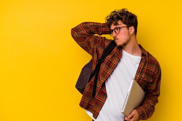 頭の後ろに触れて、考えて、選択をする黄色の背景で隔離のラップトップを保持している若い学生白人男性。