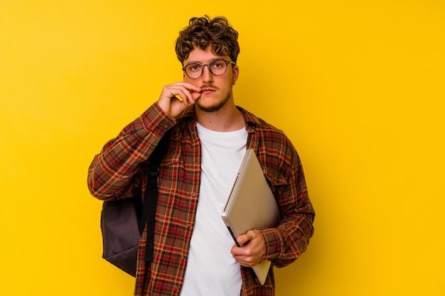 秘密を保持している唇に指で黄色の背景に分離されたラップトップを保持している若い学生白人男性。