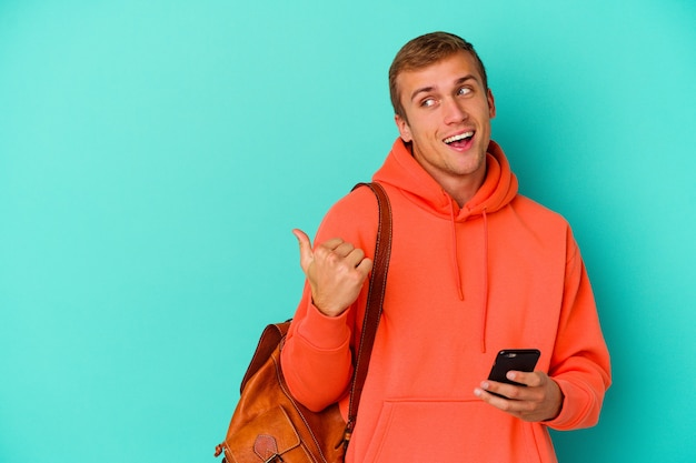 젊은 학생 백인 남자 엄지 손가락으로 멀리, 웃음과 평온한 파란색 벽 점에 고립 된 휴대 전화를 들고.