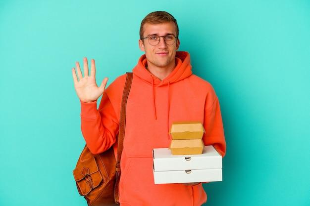 青い背景にハンバーガーとピザを保持している若い学生の白人男性は、指で 5 番を示す陽気な笑顔を浮かべています。