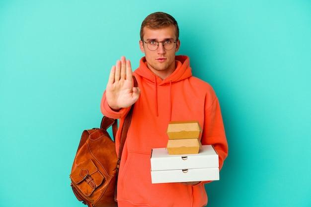 青い壁に孤立したハンバーガーとピザを持っている若い学生の白人男性は、一時停止の標識を示している手を伸ばして立って、あなたを防ぎます。