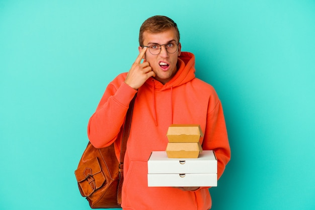 Young student caucasian man holding hamburgers and pizzas isolated on blue background showing a disappointment gesture with forefinger.